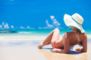 Woman with a white hat laying on the beach