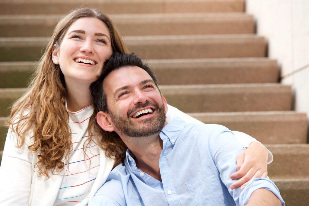 close-up-happy-couple-sitting-together-on-numvxc5-1024x683